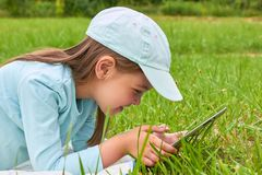 Cute baby lies on grass and plays computer Royalty Free Stock Photography