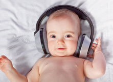Cute baby listens to music through headphones. Stock Image