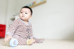 Cute Baby look left and take his feeding bottle Royalty Free Stock Photography