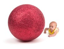 Cute Baby looking at a Huge Christmas Ornament on white Stock Photo