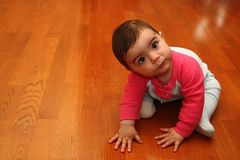 Cute baby looking up. Cute baby sitting on harfwood floor stock image
