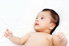 Cute baby is looking up to someone on white bed. Stock Photos