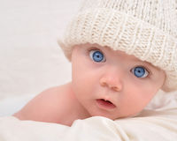 Cute Baby Looking with White Hat. A cute little baby is looking into the camera and is wearing a white hat. The baby could be a boy or girl and has blue eyes