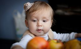 Cute baby looks on juicy red apples. Little girl reaching out for an apple.  stock photo