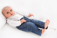 Cute baby lying barefoot on white sofa wearing blue denim jeans. Alone and sad Stock Photo