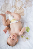Cute baby lying on bed in bedroom. At home Stock Photography