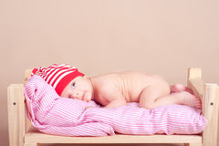 Cute baby lying in bed on beige Royalty Free Stock Images