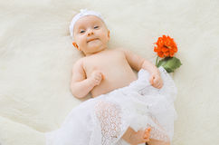 Cute baby lying on a bed with flower. Top view Stock Image