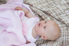 Cute baby lying on blanket. High angle view of a cute baby lying on blanket Royalty Free Stock Images