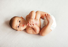 Cute baby lying on blanket and holding legs Royalty Free Stock Images