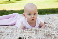 Cute baby lying on blanket at park. Close-up portrait of a cute baby lying on blanket at the park Stock Image