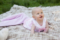 Cute baby lying on blanket at the park. Portrait of a cute baby lying on blanket at the park Stock Images