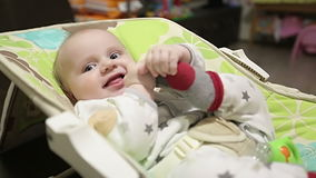 Cute baby lying in a children`s rocking chair and tries to lift his sock. stock footage