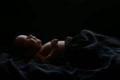 Cute baby lying covered with black fabric, isolated on black. Cute newborn baby shot in studio lying, covered with soft black blanket, isolated on black Stock Photos