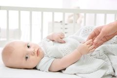 Cute baby lying in cradle and holding mother`s hand. Insomnia and sleep disorders concept Royalty Free Stock Photos