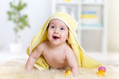 Cute baby lying on fur bed while smiling under Stock Photo