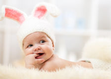 Cute baby lying on fur blanket and wearing a hat in the form of a Christmas bunny with pink ears. Cute baby girl lying on fur blanket and wearing a hat in the Stock Photography