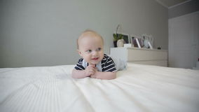 Cute baby lying on his stomach on the big bed. stock video footage