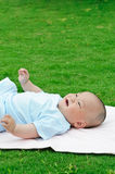 Cute baby lying on the lawn Royalty Free Stock Photos