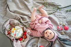Baby lying on linen blanket and wearing a hat in the form of a Easter bunny with eggs willow branches and Easter pie stock photography