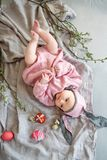 Baby lying on linen blanket and wearing a hat in the form of a Easter bunny with eggs willow branches and Easter pie royalty free stock photography
