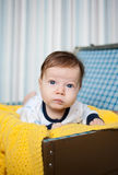 A cute baby lying on yellow knitted wrap Stock Photography
