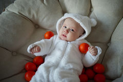 Cute baby with many tangerines Stock Photo