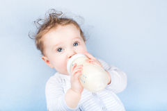 Cute baby with a milk bottle on a blue blanket Stock Photo