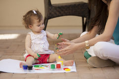 Cute baby and mom painting outside Royalty Free Stock Photos