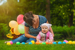 Cute baby and mom are playing on the green grass Royalty Free Stock Photography