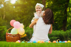Cute baby and mom are playing on the green grass Stock Photography