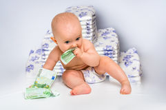 Cute baby with money isolated on blurry diapers background Stock Photography