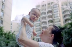 Cute baby and mother. It is a chinese mother holding his cute baby up. Photo by film Stock Photos