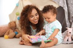 Cute baby and mother playing on floor Stock Images