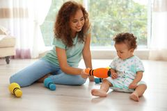 Cute baby and mother playing on floor Stock Image