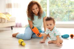 Cute baby and mother playing on floor Stock Photo