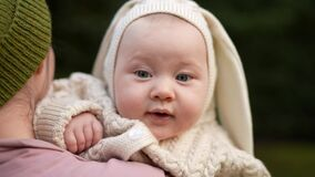 Cute baby in the mother's hands in summer nature. A joyful lifestyle of a happy mixed-race family. A young asian woman