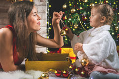 Cute baby and mum decorating a Christmas tree. Red balls. Royalty Free Stock Images