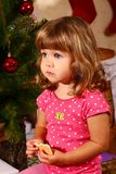 Cute baby with New Year or Christmas tree. Cute baby sitting near New Year or Christmas tree and eating cookies royalty free stock images