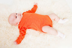 Cute baby in orange body. Laying Royalty Free Stock Images