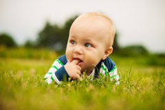 Cute baby outdoors. Adorable baby holding finger in his mouth outdoors in sunlight Royalty Free Stock Photo