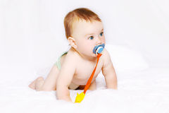 Cute baby with pacifier on the bed Royalty Free Stock Photo