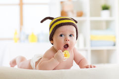 Cute baby with pacifier on the bed at home. Cute baby wered funny knitted hat with pacifier on the bed at home stock photography