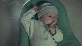 Cute baby with a pacifier in his mouth lying in a cot. Illumination is slowly becoming brighter. The child pulls a pacifier and begins to cry stock video