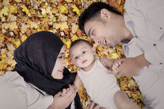 Cute baby and parents on autumn leaves Royalty Free Stock Photo
