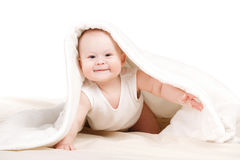 Cute baby peeking out from under the blanket. Royalty Free Stock Photography