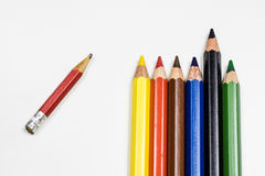 Cute baby pencil crayons on a white table. Isolated background. Stock Photos