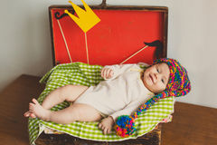 The cute baby with photo props  paper crown mustache  in wooden suitcase Royalty Free Stock Photos
