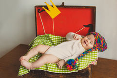 The cute baby with photo props  paper crown mustache  in wooden suitcase. Cute baby boy with fun handmade hat and photo props , Decorations , paper crown Stock Image