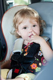 Cute baby picks his nose. While sitting in the car seat stock photography